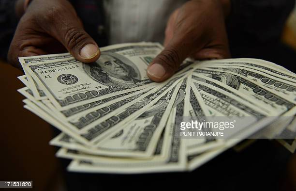 An Indian man displays US dollar notes at a local currency exchange shop in Mumbai on June 26 2013 India's rupee touched a record low of more than 60...