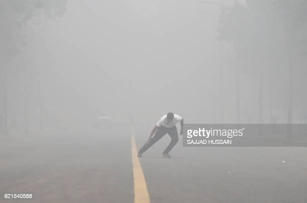 An Indian man does morning exercises on a road as heavy smog covers New Delhi on November 7 2016 Schools in the Indian capital will be closed for the...