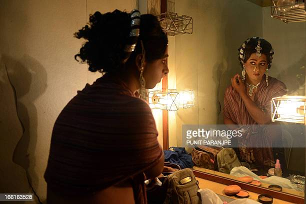 An Indian man dressed as a female gets ready for the 'Lavani' performance in Mumbai on April 8 2013 Lavani is a genre of music a combination of...