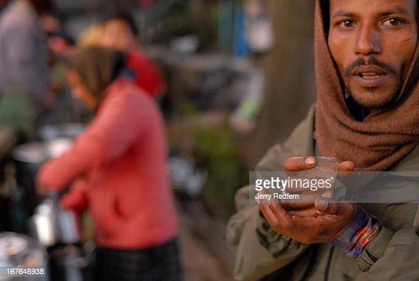 An Indian man drinks hot spiced tea on Chowrasta plaza in the gathering dark of evening The plaza is the traditional heart of Darjeeling and is...