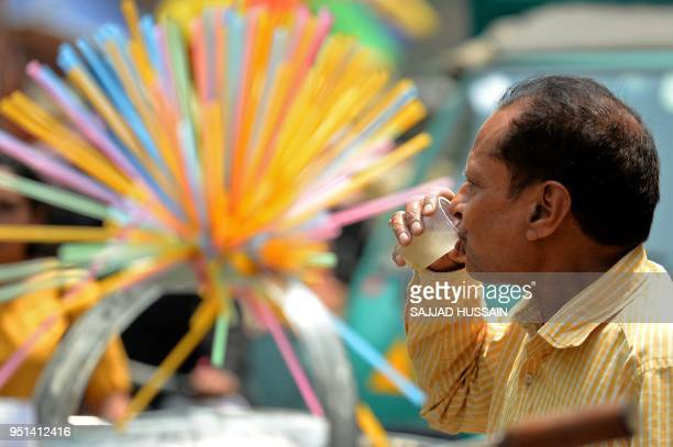 An Indian man drinks lemon water on a hot summer day in the old quarters of New Delhi on April 26 2018