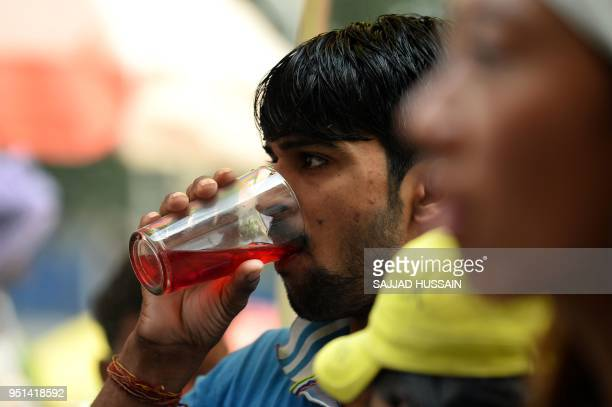 An Indian man drinks 'Sharbat' a drink made of fruits during a hot summer day in the old quarters of New Delhi on April 26 2018