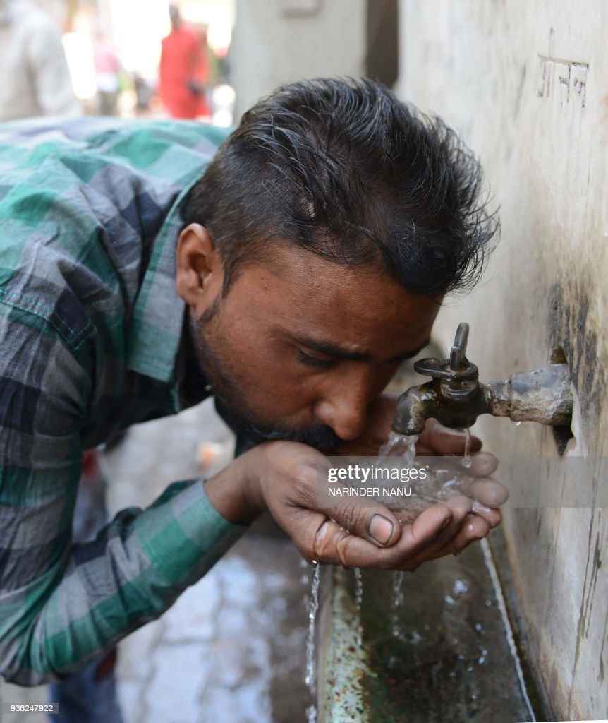An Indian man drinks water from a tap outside a temple in Amritsar on March 22 2018 World Water Day is observed on March 22 and focuses on the...