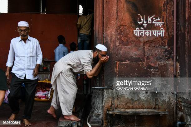 An Indian man drinks water inside the Jama Masjid in the old quarters of New Delhi on March 21 2018 Slum dwellers depend on government supplies for...