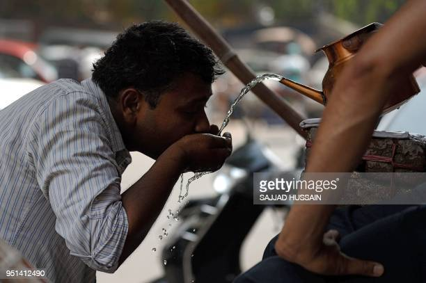 An Indian man drinks water on a hot summer day in the old quarters of New Delhi on April 26 2018