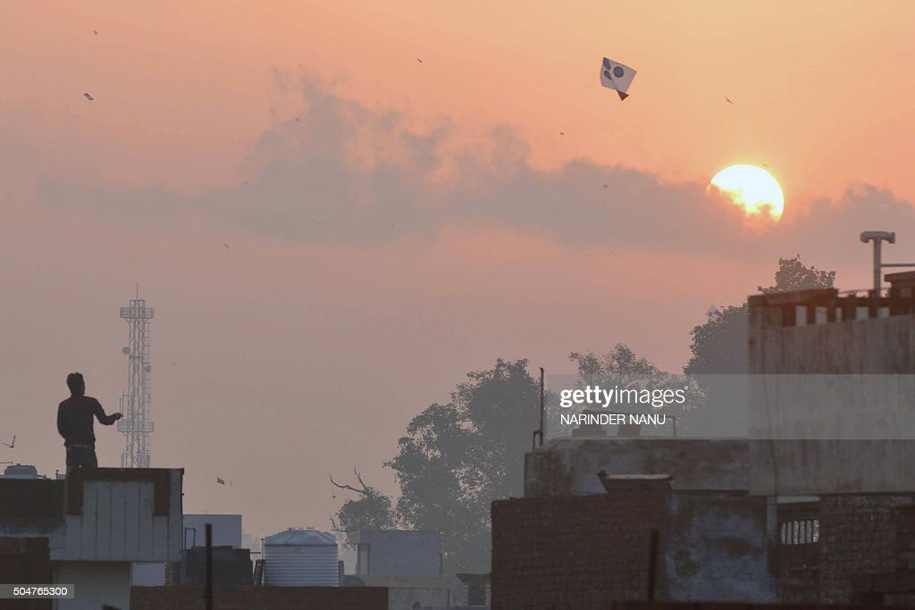 TOPSHOT An Indian man flies a kite during celebrations for the Lohri festival in Amritsar on January 13 2016 The Lohri harvest festival which falls...