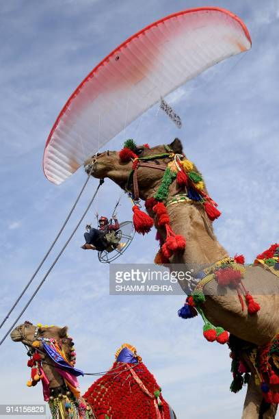 An Indian man flies with his powered paragliding during the last day of Kila Raipur Games known as the rural Olympics at Kila Raipur on the outskirts...