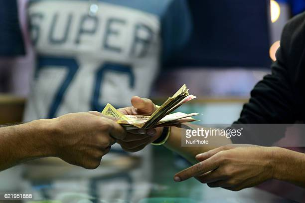 An indian man gives his 1000 and 500 rupee notes to a retail shopkeeper in Allahabad on November 92016 Indian Prime Minister Narendra Modi announced...