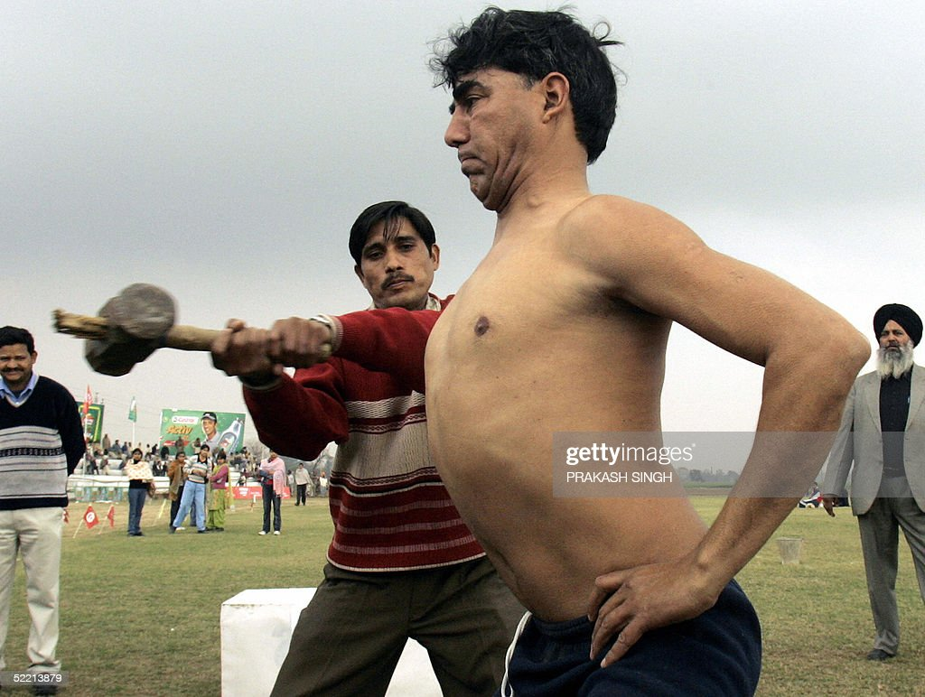 An Indian man hammers on the chest of villager Subash Chandra Sharma at the Kila Raipur rural games near Ludhiana in India`s northern state of Punjab.