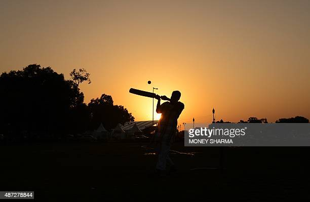 An Indian man hits a shot as he plays cricket with others near the India Gate monument in New Delhi on September 8 2015 AFP PHOTO / MONEY SHARMA