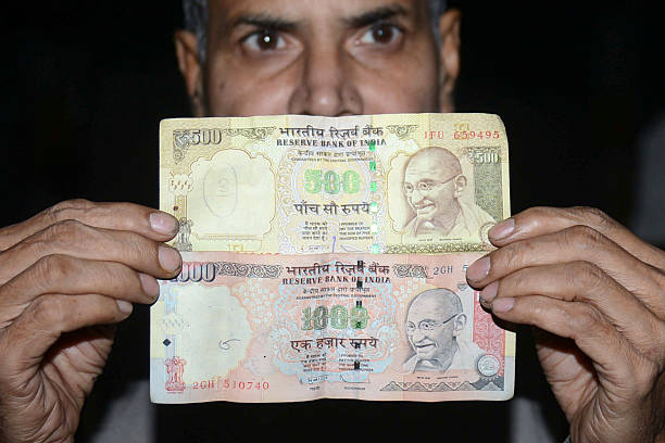 An Indian man holds 500 and 1000 INR notes in Amritsar on November 8 2016 Indian Prime Minister Narendra Modi announced late November 8 that 500 and..