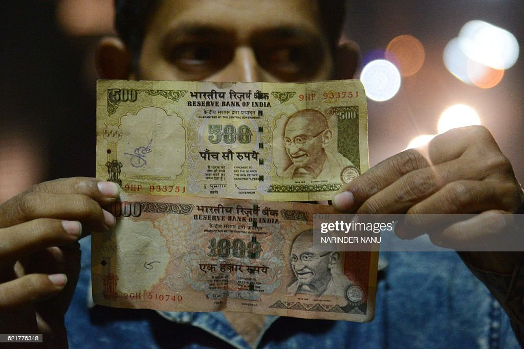An Indian man holds a 500 and 1000 Indian Rupee banknotes in Amritsar on November 82016 Indian Prime Minister Narendra Modi announced late November 8.