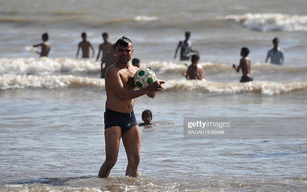 An Indian man holds a football at Juhu beach in Mumbai on June 6, 2010. AFP PHOTO/Sajjad HUSSAIN