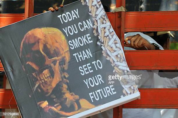An Indian man holds an antismoking poster on World No Tobacco Day in Mumbai on May 31 2010 According to the WHO there are more than one billion...
