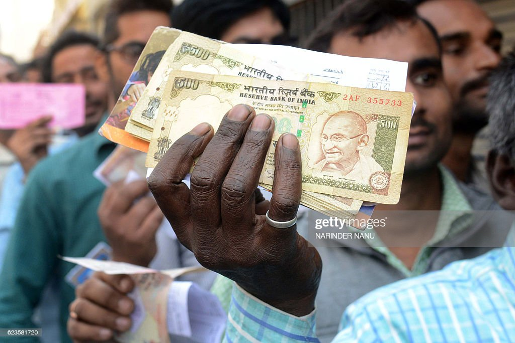 An Indian man holds up money to be exchanged as people wait in a queue to deposit and exchange 500 and 1000 rupee notes outside a bank in Amritsar on.