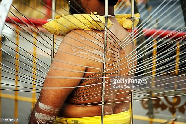 CONTENT] An Indian man in a large kavadi has numerous large needles piercing into his body supporting the weight of the sacrifice he carries during...