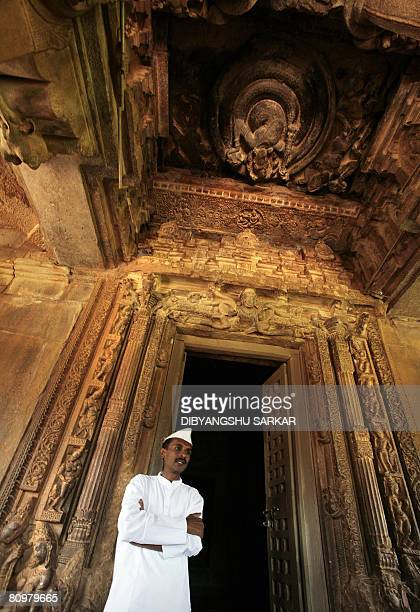 An Indian man in traditional dress stands by the doorway of the temple dedicated to the Hindu godess Durga at Aihole near the southern Indian city of...
