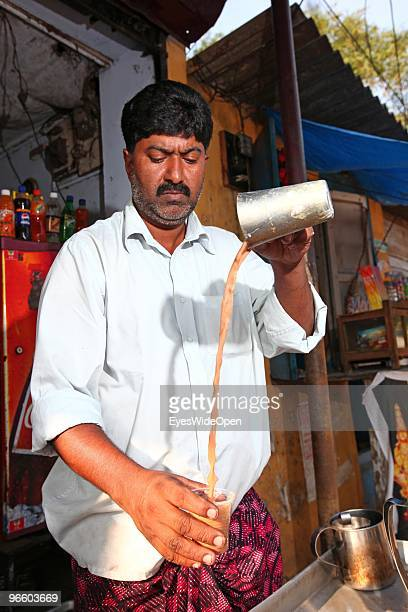 An indian man is preparing traditional chai masala milk tea at his chai stall in Kumily on January 02 2010 in Kumily near Trivandrum Kerala South...