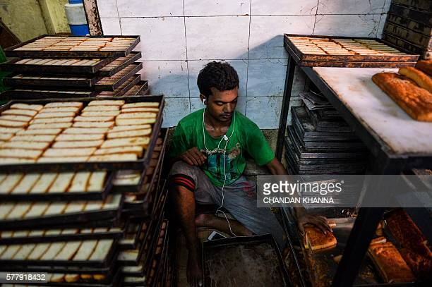 An Indian man listens to music on earphones as he works at a local bakery in the old quarters of New Delhi on July 20 2016 / AFP / CHANDAN KHANNA
