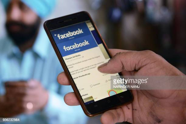 An Indian man looks at the Facebook app on his smartphone in Amritsar on March 22 2018 / AFP PHOTO / NARINDER NANU