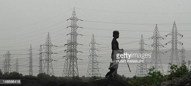 An Indian man looks at towers carrying electricity power cables in Mumbai on July 31 2012 A massive power failure hit India for the second day...