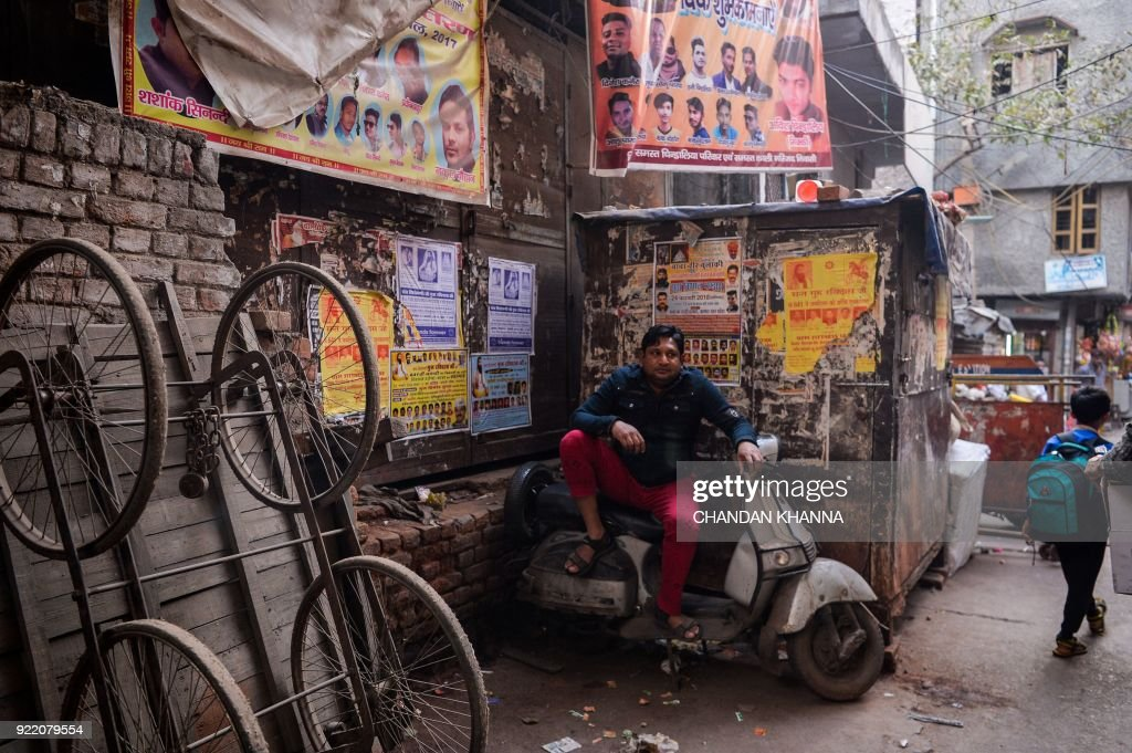 An Indian man looks on as he sits on a scooter in the old quarters of New Delhi on February 21, 2018. /