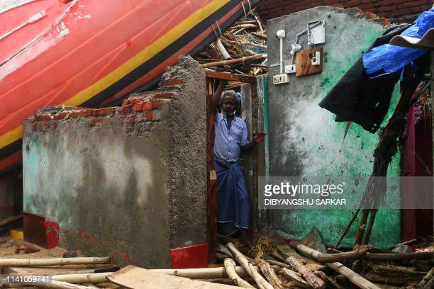 An Indian man looks out from a damaged building with a fishing boat lodged on the roof along the seafront in Puri in the eastern Indian state of...