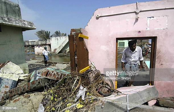An Indian man looks through a door of his damaged home in Nagapattinamsome 350 km south of Madras 29 December 2004 after tidal waves hit the region...