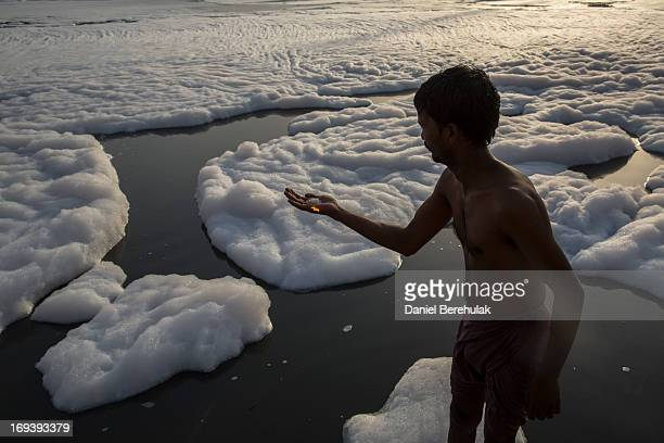 An Indian man makes an offering on the banks of an industrial wastefoam polluted section of the Yamuna River on the outskirts of New Delhi on May 24...