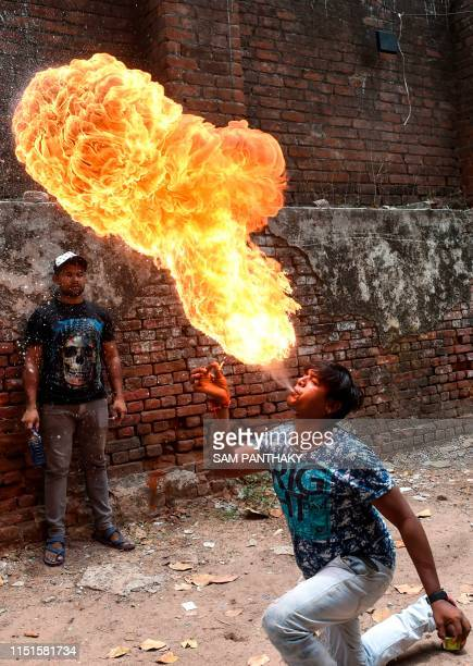 An Indian man Nitinbhai Lodha spits fire during the rehearsal for the forthcoming Lord Jagannath Rath Yatra an annual Hindi festival in Ahmedabad on...