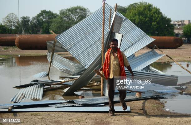 An Indian man passes next to a destroyed tin shed near a construction site following a major storm in Allahabad on May 3 2018 Powerful dust storms...