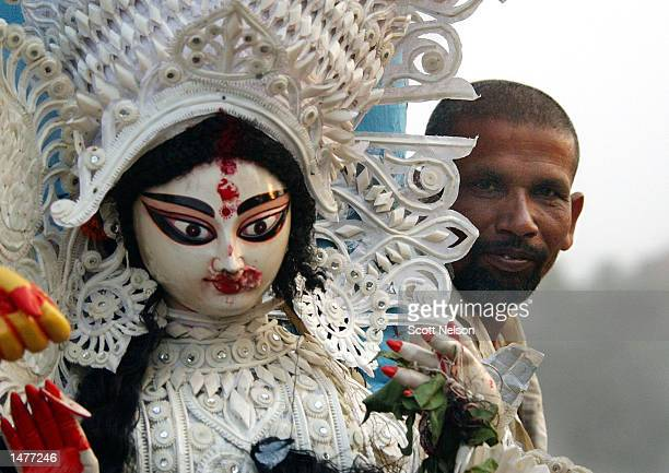 An Indian man peers out from behind a statue of the Hindu goddess Durga during a celebration marking the end of the Durga Puja festival October 15...