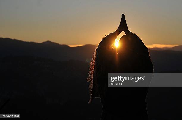 An Indian man performs 'Surya Namaskar' Salute to the Sun during the first sunrise of the year 2015 in the northern hill town of Shimla on January 1...