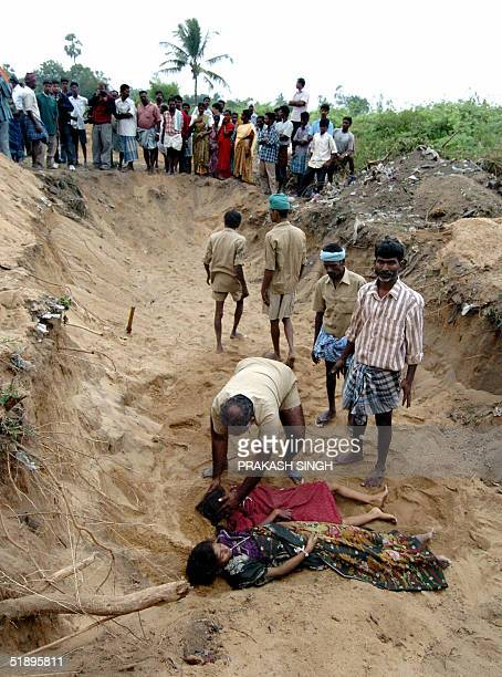 An Indian man places the dead body of a girl in a mass burial site at Silver Beach in Cuddaloresome 185 kms south of Madras 27 December 2004 after...