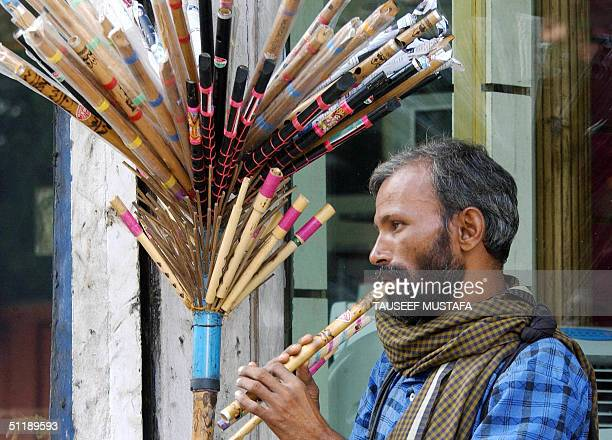 An Indian man plays flute to attract customers at his roadside stall, in Srinagar 19 August 2004. Life goes on in Indian Kashmir, despite daily...
