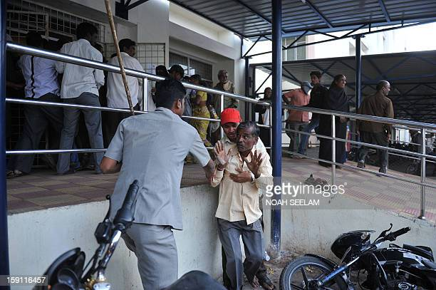 An Indian man pleads with the police as they disperse supporters of the MajliseIttehadul Muslimeen party after the arrest of their leader Akbaruddin...