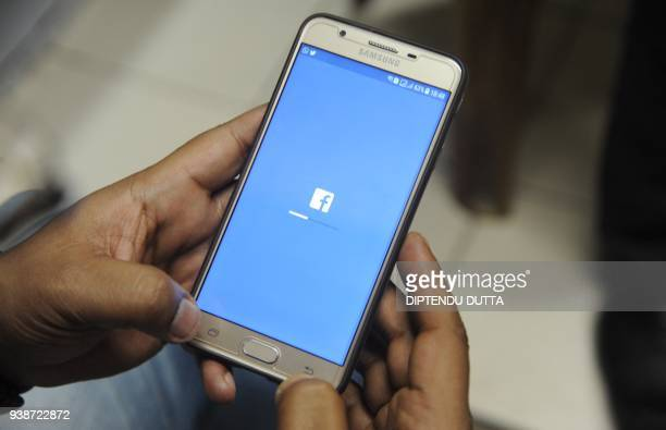 An Indian man poses for a photograph using Facebook on his cellpohne in Siliguri on March 27 2018 India's ruling and main opposition parties on March...