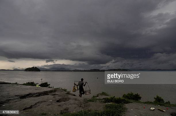 An Indian man prepares to collect water as rain clouds loom over the Brahmaputra River in Guwahati capital of northeastern Assam state on April 22...
