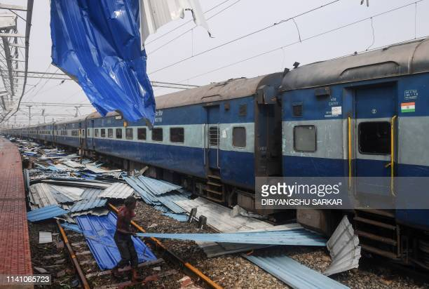An Indian man pulls a piece of debris on the train tracks at the damaged railway station in Puri in the eastern Indian state of Odisha on May 4 after...