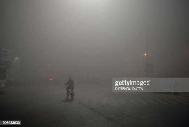 TOPSHOT An Indian man rides a bicycle amid heavy smog in Siliguri on January 19 2018 / AFP PHOTO / DIPTENDU DUTTA