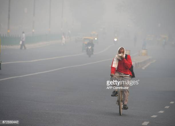 An Indian man rides a bike amid heavy smog on a street of New Delhi on November 10 2017 Large swathes of India's northern states remained under dense...