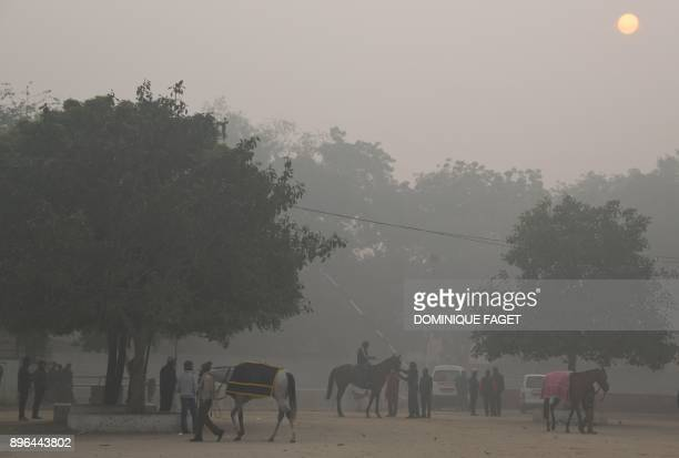 An Indian man rides a horse amid heavy smog at the Delhi Race Club in New Delhi on December 21 2017 / AFP PHOTO / Dominique Faget