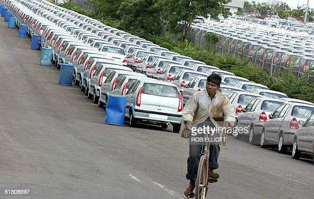 An Indian man rides his bicyle along a line of new Tata cars at the Tata Motors factory in Pune 14 September 2004 India's leading automotive...