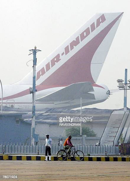 An Indian man rides his cycle past the tail of an Air India plane at the airport in New Delhi 22 November 2007 Six Air India flights out of Delhi's...