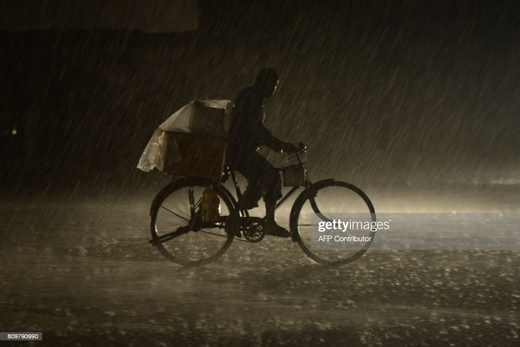 An Indian man rides on a bike as heavy rain falls in Jalandhar on July 6 2017 / AFP PHOTO / SHAMMI MEHRA