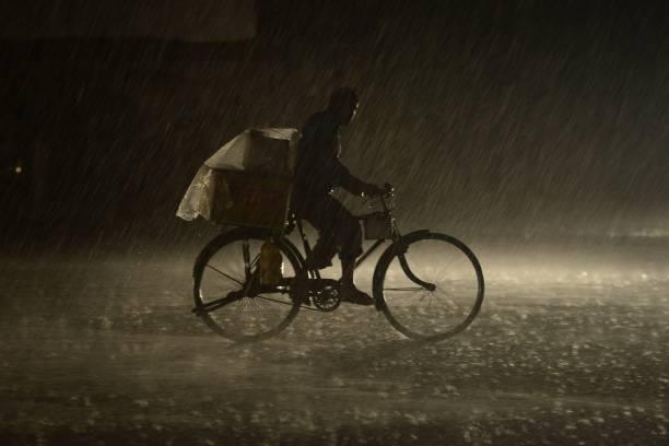 An Indian man rides on a bike as heavy rain falls in Jalandhar on July 6 2017 / AFP PHOTO / SHAMMI MEHRA