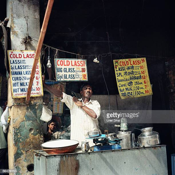 An Indian man sells lassi a traditional yoghurt drink and milk from his roadside stall September 26 2005 in New Delhi India Although India occupies...