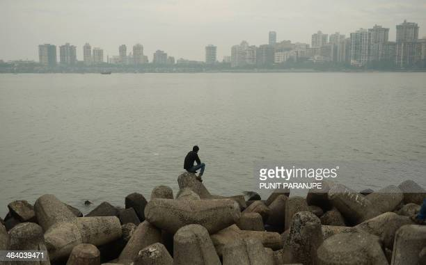 An Indian man sits at the sea front on a hazy afternoon in Mumbai on January 20 2014 AFP PHOTO/ PUNIT PARANJPE