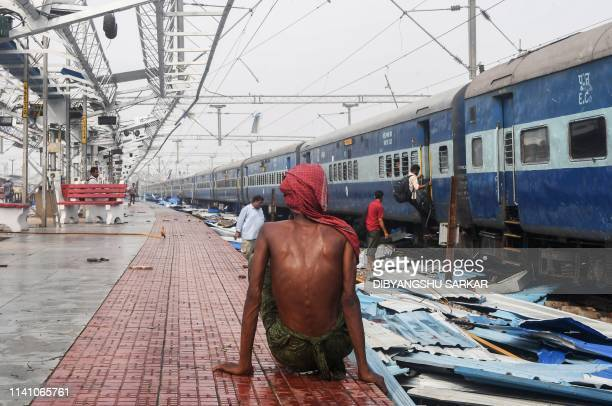 TOPSHOT An Indian man sits on the train station platform as people look through debris on the tracks at the damaged railway station in Puri in the...