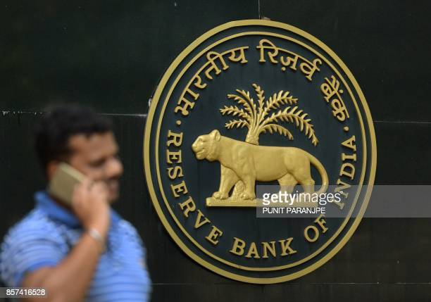 An Indian man speaks on a phone near the Reserve Bank of India logo at the head office in Mumbai on October 4 2017 India's central bank held interest...